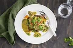 Chicken leg in creamy coriander pesto sauce served on sweet potato and zucchini Stock Image