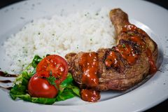 Chicken leg in hot sauce. With rice, tomatoes and ricola on the side Royalty Free Stock Images