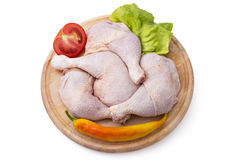 Chicken leg quarters. Fresh raw chicken legs arrangement on kitchen cutting board with lettuce, tomato and pepper Royalty Free Stock Photos