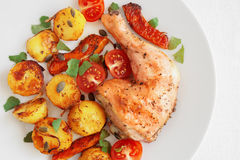 Chicken leg roasted with potato and pumpkin served with tomatoes, cilantro, and pumpkin seeds Stock Photo