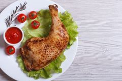 Chicken leg with rosemary, lettuce and tomato. top view. Roasted chicken leg with rosemary, lettuce and tomato on a white plate. top view royalty free stock photo