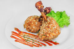 Chicken legs. Fried breaded chicken legs in oat flakes with salad and ketchup in white dishes Stock Photo