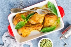 Chicken legs. Baked chicken legs with fresh basil leaves stock images