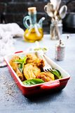 Chicken legs. Baked chicken legs with fresh basil leaves royalty free stock photo