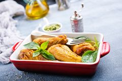 Chicken legs. Baked chicken legs with fresh basil leaves royalty free stock images
