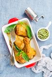 Chicken legs. Baked chicken legs with fresh basil leaves royalty free stock photos