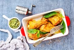 Chicken legs. Baked chicken legs with fresh basil leaves stock photos