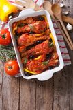 Chicken legs baked in tomato sauce vertical top view close-up Stock Image