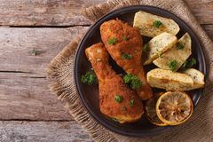 Chicken legs in batter, with potato on the plate closeup. top vi Stock Photography