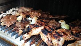 Chicken legs and beef on grill. Barbeque at work: mushrooms, beef, mutton, chicken legs, onion and greasy juice from them all. Yum, yum Royalty Free Stock Photo