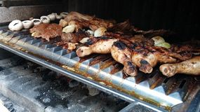 Chicken legs and beef on grill. Barbeque at work: mushrooms, beef, mutton, chicken legs, onion and greasy juice from them all. Yum, yum royalty free stock photography