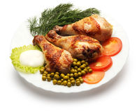 Chicken legs decorated with dill, pea and tomato. Over white background Royalty Free Stock Image