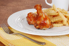 Chicken legs and french fries with barbecue sauce Stock Image