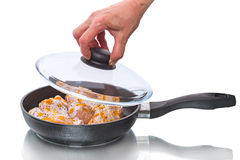 Chicken legs in a frying pan with glass lid Stock Images