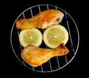 Chicken legs on the grill with sliced lemon view from above on black Stock Photo