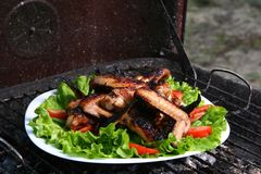 Chicken legs on the grill with vegetables Stock Image