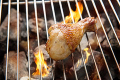 Chicken legs grilling over flames on a barbecue. Royalty Free Stock Photography