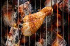 Chicken legs grilling over flames on a barbecue. Royalty Free Stock Image