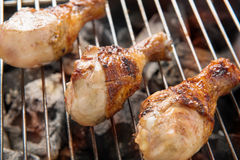 Chicken legs grilling over flames on a barbecue. Royalty Free Stock Images