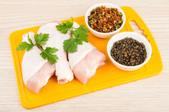 Chicken legs with parsley on plastic board, bowls with spices Royalty Free Stock Photography