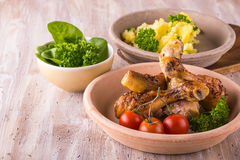 Chicken legs on plate in front of  potatoes and green salad Royalty Free Stock Photos