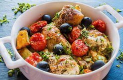 Chicken legs with potatoes, cherry tomatoes and black olives. White baking dish on dark stone background Royalty Free Stock Photography