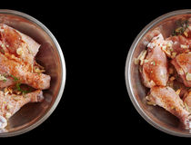 Chicken legs raw. Isolated black background. Chicken legs on the plate with spices Stock Photos
