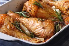 Chicken legs with rosemary in a baking dish macro horizontal Royalty Free Stock Images