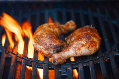 Chicken legs spiced by special spice blend. On bbq grill with flame stock photo