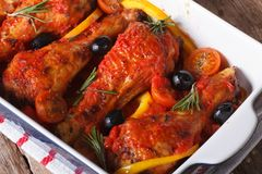 Chicken legs in tomato sauce in a baking dish closeup top view. Chicken legs in tomato sauce with vegetables in a baking dish closeup. horizontal view from above Royalty Free Stock Photography