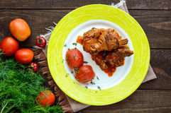 Chicken legs with tomato sauce and marinated tomatoes without skins in their own juice. Stock Photography