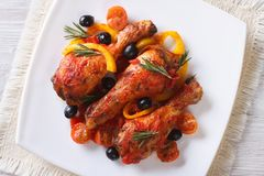 Chicken legs in tomato sauce on a plate, horizontal top view Royalty Free Stock Photo