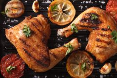 Chicken legs and vegetables on grill macro. Top view horizontal Stock Image