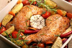 Chicken legs with vegetables and herbs ready for roasting.  Royalty Free Stock Photography