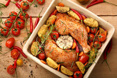 Chicken legs with vegetables and herbs ready for roasting.  Stock Photo