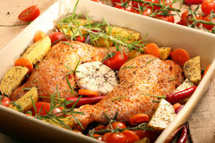 Chicken legs with vegetables and herbs ready for roasting.  Stock Photos