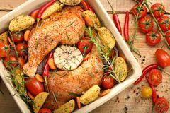 Chicken legs with vegetables and herbs ready for roasting.  Stock Photography