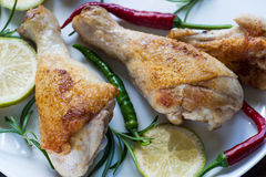 Chicken legs on white plate with rosemay and lime royalty free stock image