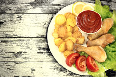 Chicken legs on a white plate with slices tomato and lettuce and french fries and ketchup on wooden board table vintage. Background. Top view. Old style stock images