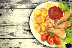Chicken legs on a white plate with slices tomato and lettuce and french fries and ketchup on wooden board table vintage. Background. Top view. Old style royalty free stock images