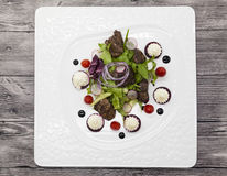 Chicken liver with balsamic sauce salad, appetizer. Hot chicken liver salad with lettuce on a plate closeup. Royalty Free Stock Photo