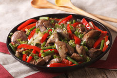 Chicken liver fried with vegetables close-up on a dish. horizont Stock Photos