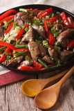 Chicken liver fried with vegetables close-up on a dish. Vertical Stock Image
