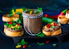 Chicken liver pate on crostini. With oregano and mixed peppers stock images