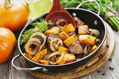 Chicken liver with pumpkin. In a frying pan on the table stock photos