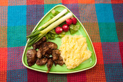 Chicken liver served with mashed potatoes, onions and radishes.  Royalty Free Stock Photo