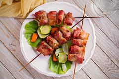 Chicken liver wrapped with bacon on skewers. Grilled liver kebabs with vegetables on white plate. Overhead, horizontal stock image