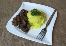 Chicken livers rice with curry. Czech Republic fried chicken liver with curry rice and a fork on a white plate Royalty Free Stock Photo