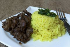 Chicken livers rice with curry detail. Photographed on Nov. 1, 2015 Jablonec nad Nisou, Czech Republic fried chicken liver with curry rice and a fork on a white Stock Images