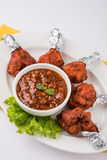 Chicken lollipop or chicken winglet. Served with tomato chutney, a chinese preparation Royalty Free Stock Image